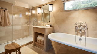 Sandstone tiled ensuite with a double shower and standalone rolltop bathtub
