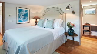 Plush pillowy king-bed in a light-filled luxury barge cabin with soft blue accents
