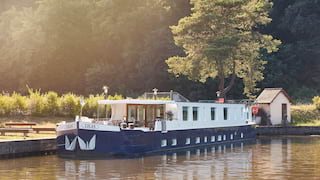 Navy-blue bottomed river barge moored on a rural canalside surrounded by trees