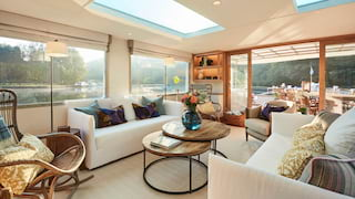 Lounge on a luxury barge with bright white soft furnishings and maple wood detailing