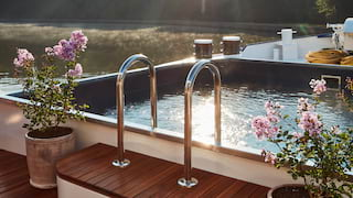 Sun rays sparkling on the surface of a plunge pool on the top deck of a luxury barge