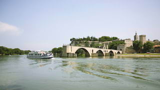 Luxurious river barge floating alongside a rural French village with rolling vineyards