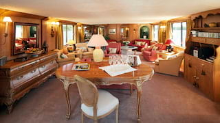 Regal lounge area of a luxury river barge with Louis XIV furniture and red accents