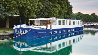 Exterior of a royal-blue bottomed river barge moored alongside a tree-lined canal