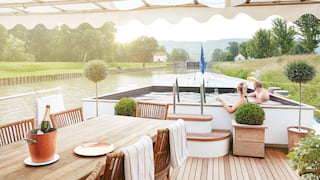 Two guests relaxing in a hot tub on the wood-panelled top deck of luxury river barge