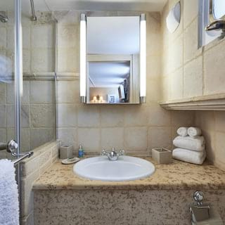 Barge cabin ensuite with a large rain shower and a beige terrazzo sink unit