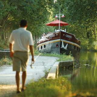 Deckhand walking along a tree-lined canalside towards a luxurious river barge
