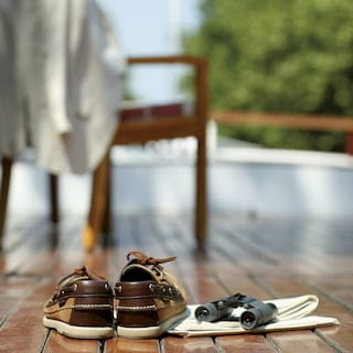 Close-up of a pair of brown leather deck shoes next to a pair of binoculars