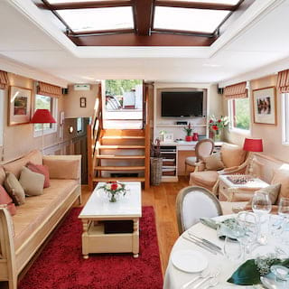 Light-filled barge lounge area with a red carpet and red pinstripe details