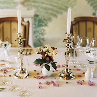 Linen-topped dining table dressed with pink rose petals and silver candle holders
