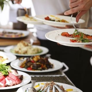 Close-up of guests spooning food from an array of buffet dishes onto their plates