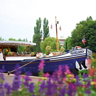 View from among pink and purple flowers of the navy blue bow of a river barge
