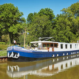 River barge with a blue painted bow and raised anchors moored alongside a canal
