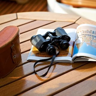 Close-up of a pair of binoculars next to a leather case on top of a magazine