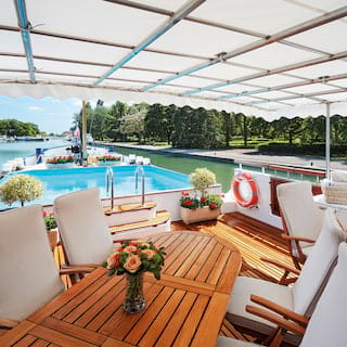 Wooden table surrounded by white fabric chairs on the top deck of a luxury barge