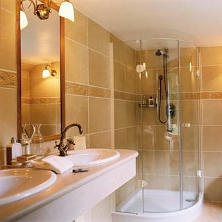 Glass corner shower in a spacious barge cabin bathroom with 'his and hers' sinks