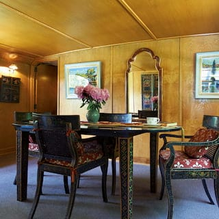 Black and gold lacquer table and chairs in a wood-panelled dining area of a barge