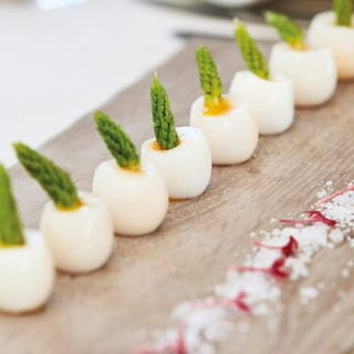 Close-up of boiled and shelled quails eggs in a row, garnished with an asparagus tip
