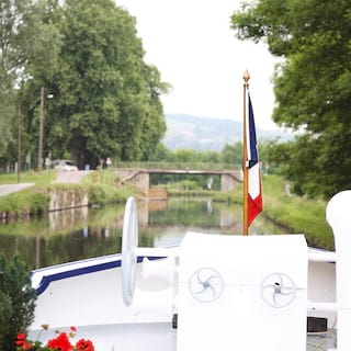 An anchor wheel, French flag and potted plants in the bow of a luxury river barge