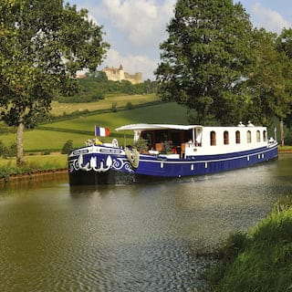 Navy and white river boat flying a French flag while gliding along a rural canal