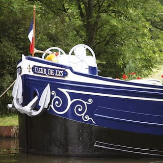 Navy and white painted bow of a river boat with a coil of rope hanging along the side