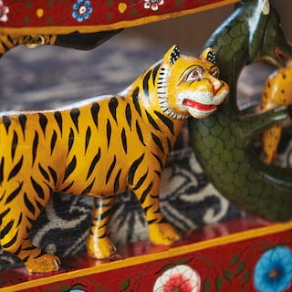 Close-up of a carved wooden tiger painted orange with black stripes