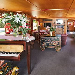 Grand wood-panelled lounge area of a luxury barge with a baby grand piano