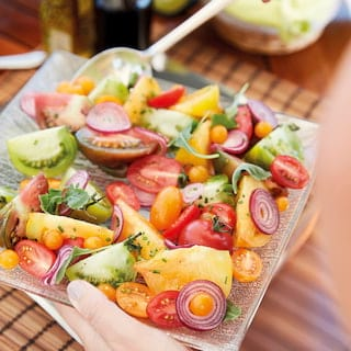 Close-up of a mixed tomato salad served with red onion and chives