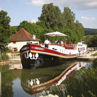 Black bottomed river barge navigating through a narrow canal in idyllic rural France