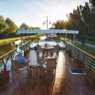 Guests relaxing with champagne on the sun-splashed top deck of a river barge