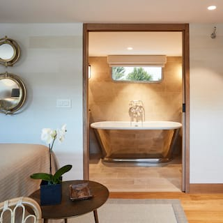 View through a door of a standalone copper rolltop bathtub from a stylish cabin