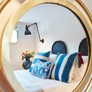Circular gold-framed mirror reflecting blue striped cushions on a king-bed