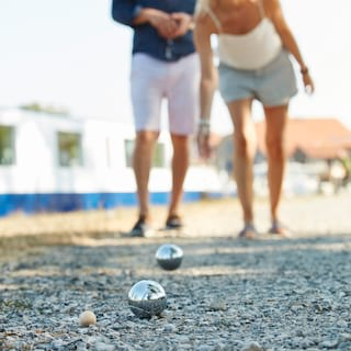 Close-up of two silver petanque balls on a stone path with the players behind