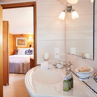 Glamorous white-tiled cabin en-suite with a ceramic sink and green product bottles