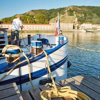 Deckhand pulling ropes onto a river barge with blue details in a rural French village