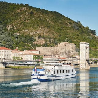 River barge sailing towards a medieval bridge leading from a small French town