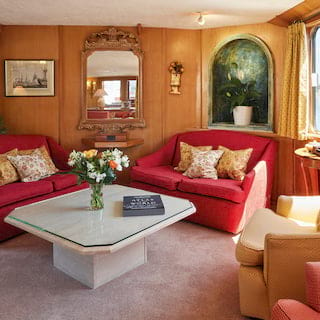 Grand lounge area of a river barge with red soft furnishings and baroque styling