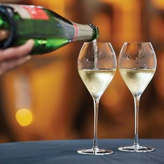 Close-up of champagne being poured from a bottle into two champagne glasses