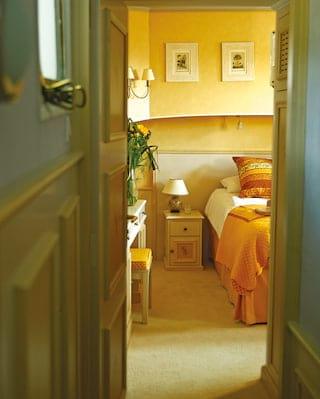 Shot along a corridor through an open door of a king-bed with an orange bedspread