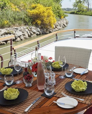 Wooden table on the top deck of a river barge set for lunch with green linen napkins