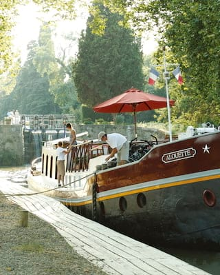 Luxury river barge moored alongside a tree-lined canal