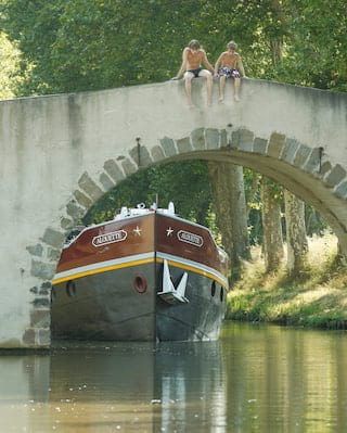 Two fishermen in hats sitting on the wall of a bridge while a barge glides underneath