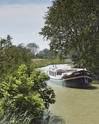 Luxury river barge with a chocolate brown bow sailing along a tree-lined river bank