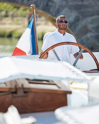 Smiling captain wearing sunglasses and a white t-shirt while steering a ship's wheel