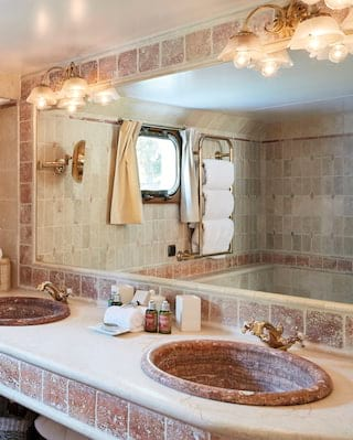 Barge cabin ensuite with red granite tiles and matching 'his & hers' sinks