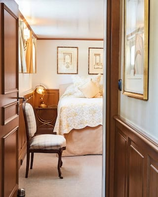 View through an open door along a corridor of a bedroom with blush pink accents