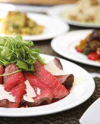 Close-up of pink slices of sirloin steak topped with parmesan and a rocket salad