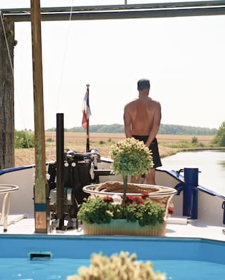 Guest standing on the bow of a luxury barge looking out at the French countryside