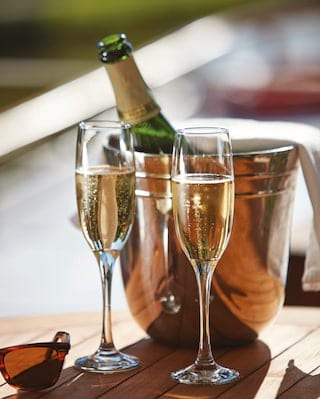 Champagne bubbles rising in two flute glasses next to a silver champagne cooler