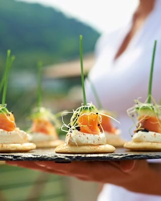 Close-up of salmon mousse and bellini canapés on a slate platter